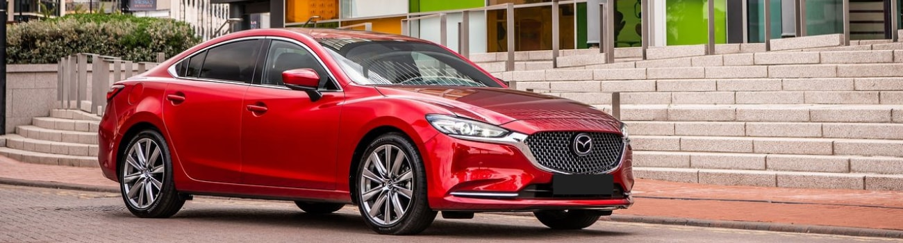 Red 2019 Mazda6 Signature parked in front of concrete steps outside a downtown courthouse