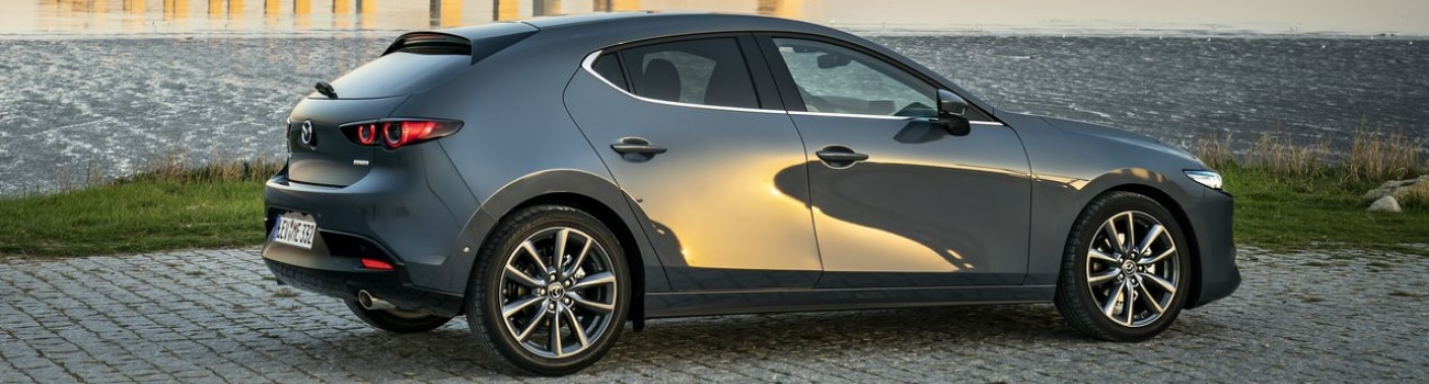 Exterior view of the passenger side on a 2019 Mazda3 Hatchback parked by the water under a bridge