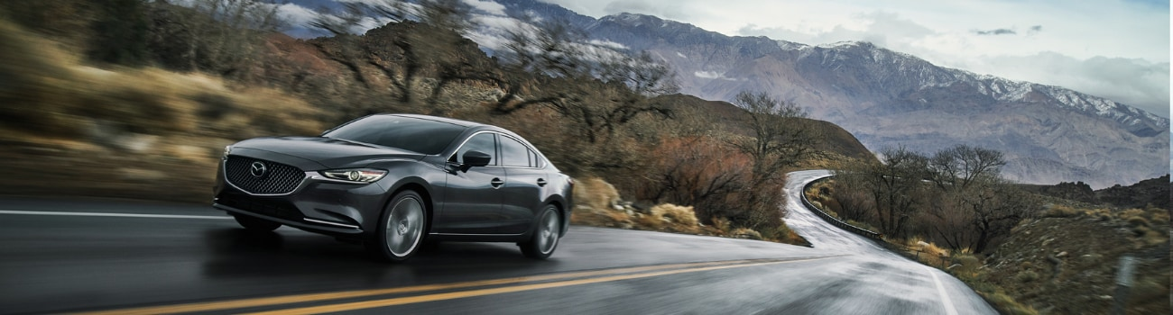2019 Mazda6 sedan driving down a wet curvy road through hills by a mountain range
