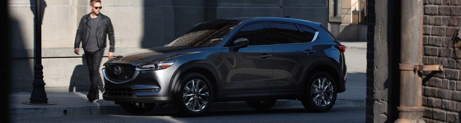 A 2019 Mazda CX-5 parked on an empty city street as the driver walks around the SUV to get in