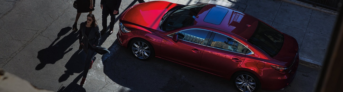 Aerial view of a red 2019 Mazda6 as civilians walk past at a crosswalk