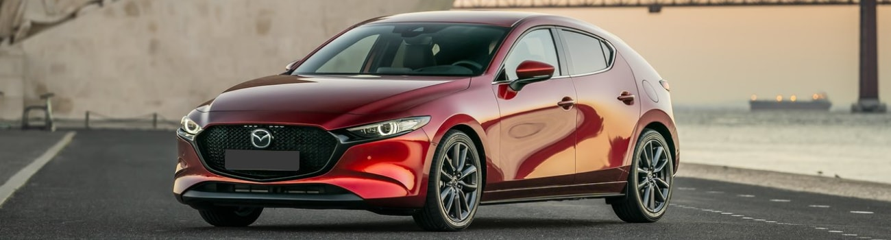 Exterior view of the driver side on a red 2019 Mazda3 hatchback parked by some docks near the water