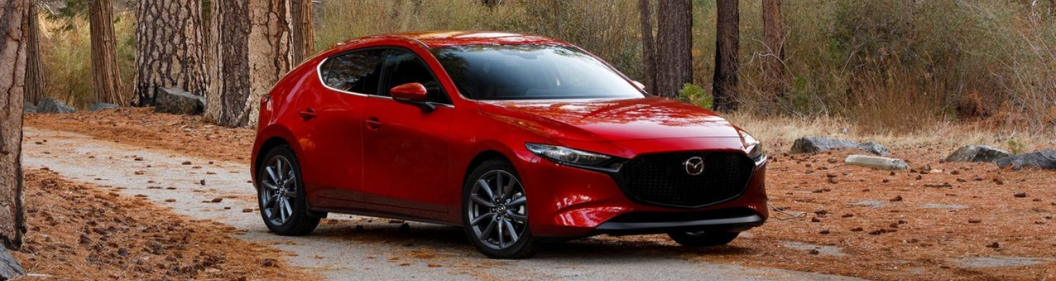 Passenger side exterior of a red 2019 Mazda3 hatchback parked in an autumn forest