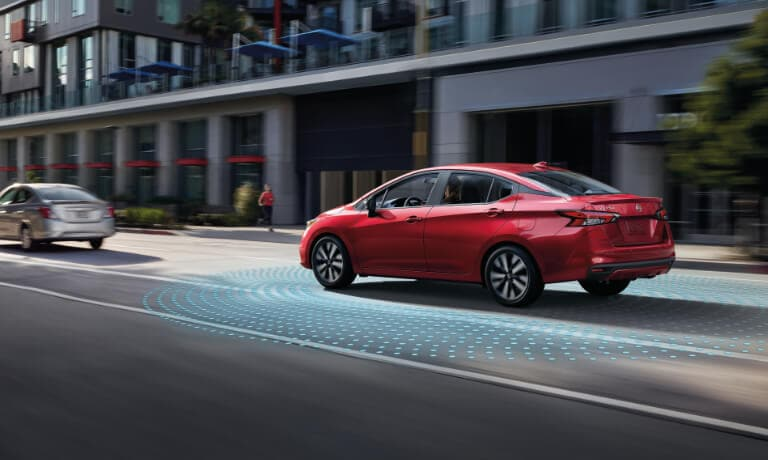 2020 Nissan Versa in red driving on a street showing saftey sensors .jpg