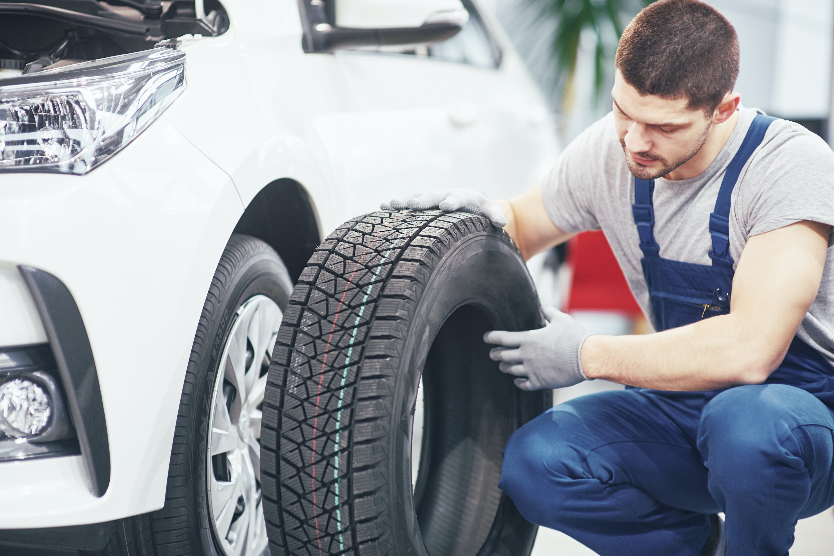 How to rotate your vehicle tires at Boch Auto Group in Massachusetts | Mechanic kneeling with tire