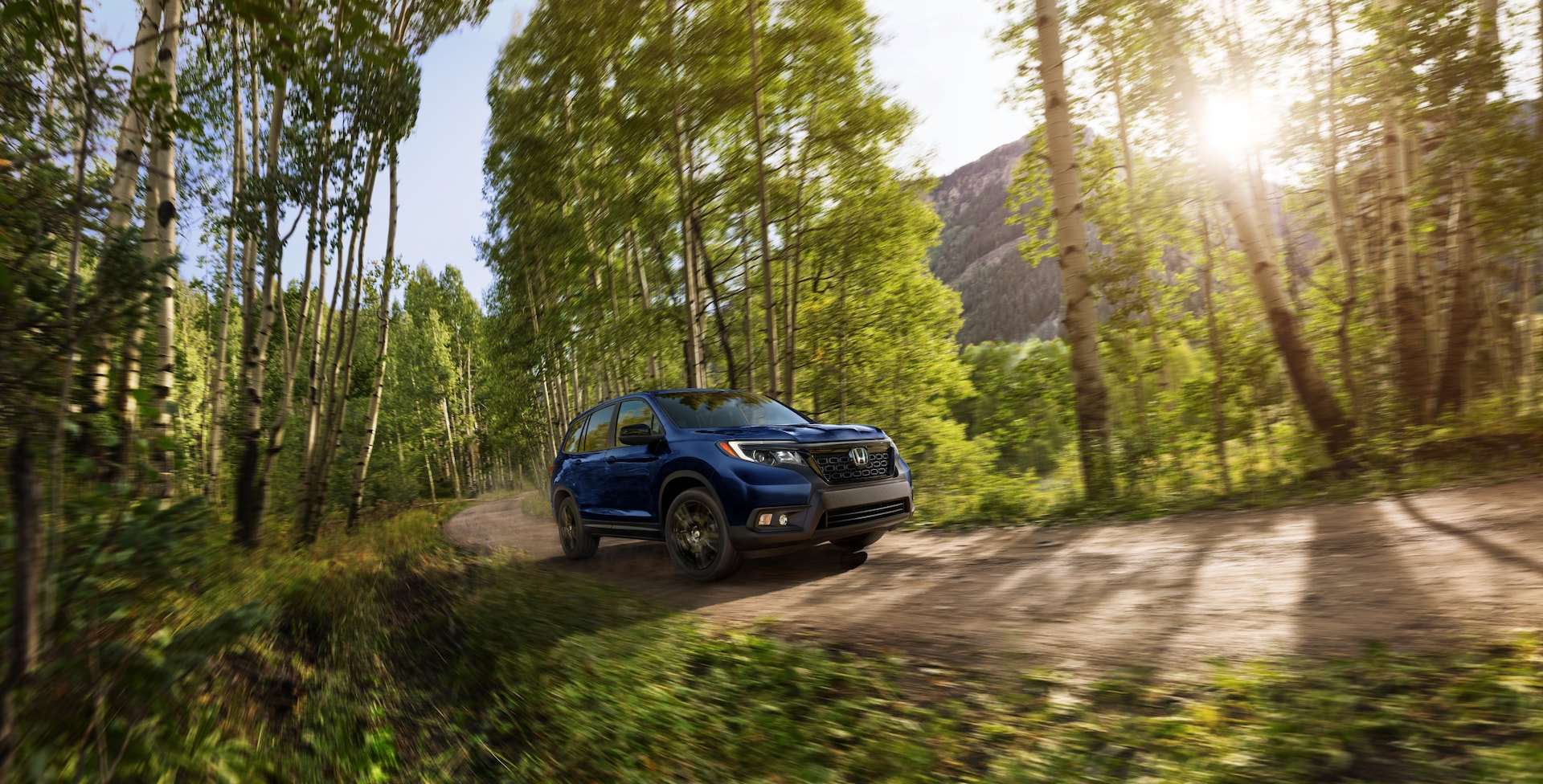 Boch Honda is a Car Dealership near Medfield, MA | Blue 2020 Honda CR-V driving through woods