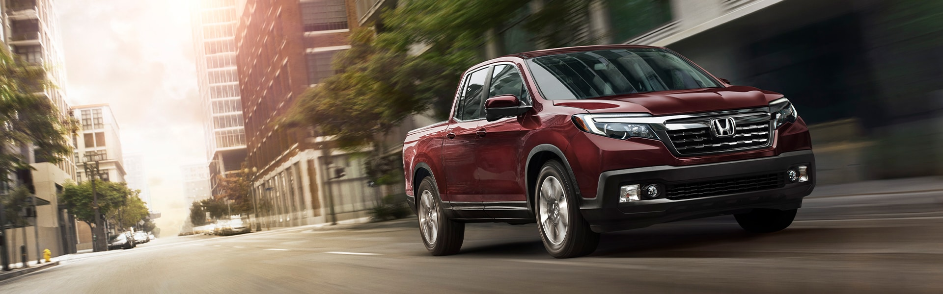 Boch Honda West is a Family Owned Dealership near Acton, MA | Red 2020 Ridgeline Driving Through City