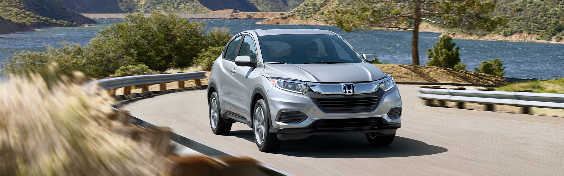 Boch Honda West is a Family Owned Dealership near Acton, MA | Silver 2020 HR-V Driving Around Bend in Front of Lake