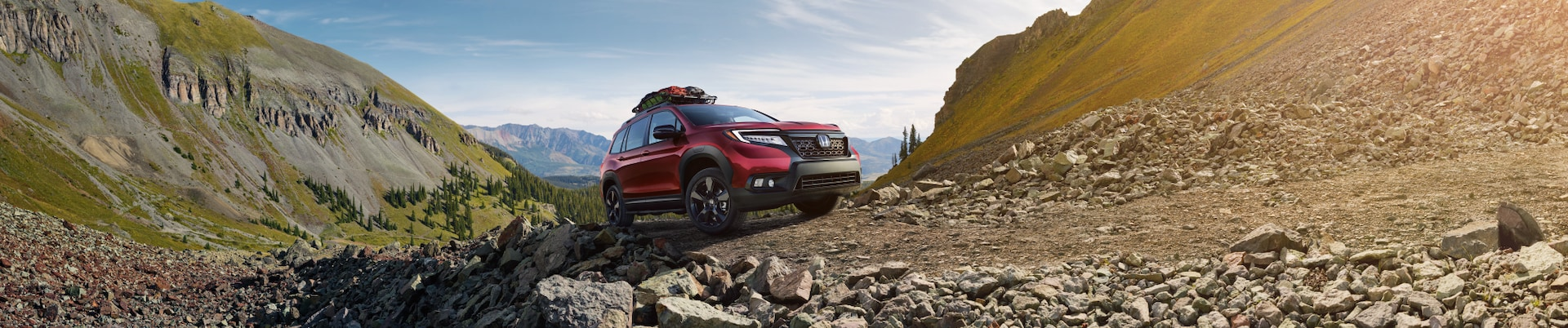Boch Honda West is a Family Owned Dealership near Boxborough, MA | Red 2020 Honda Passport driving on rocks