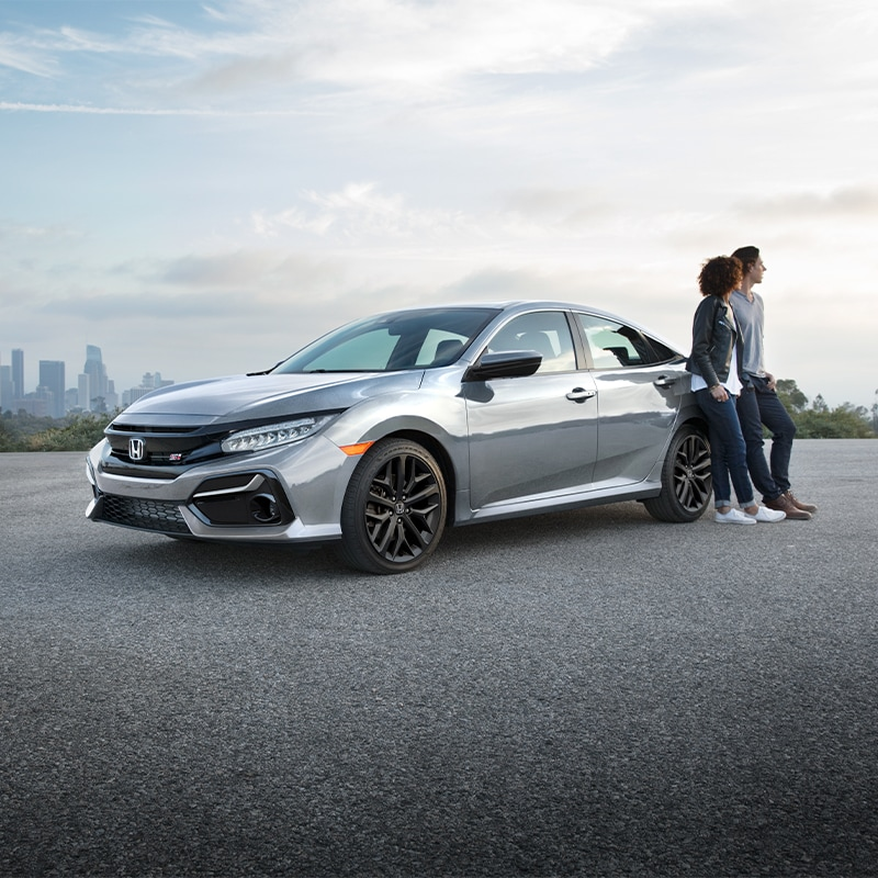 Boch Honda West is a Family Owned Dealership near Acton, MA | Couple Leaning on Silver 2020 Civic Parked in Parking Lot