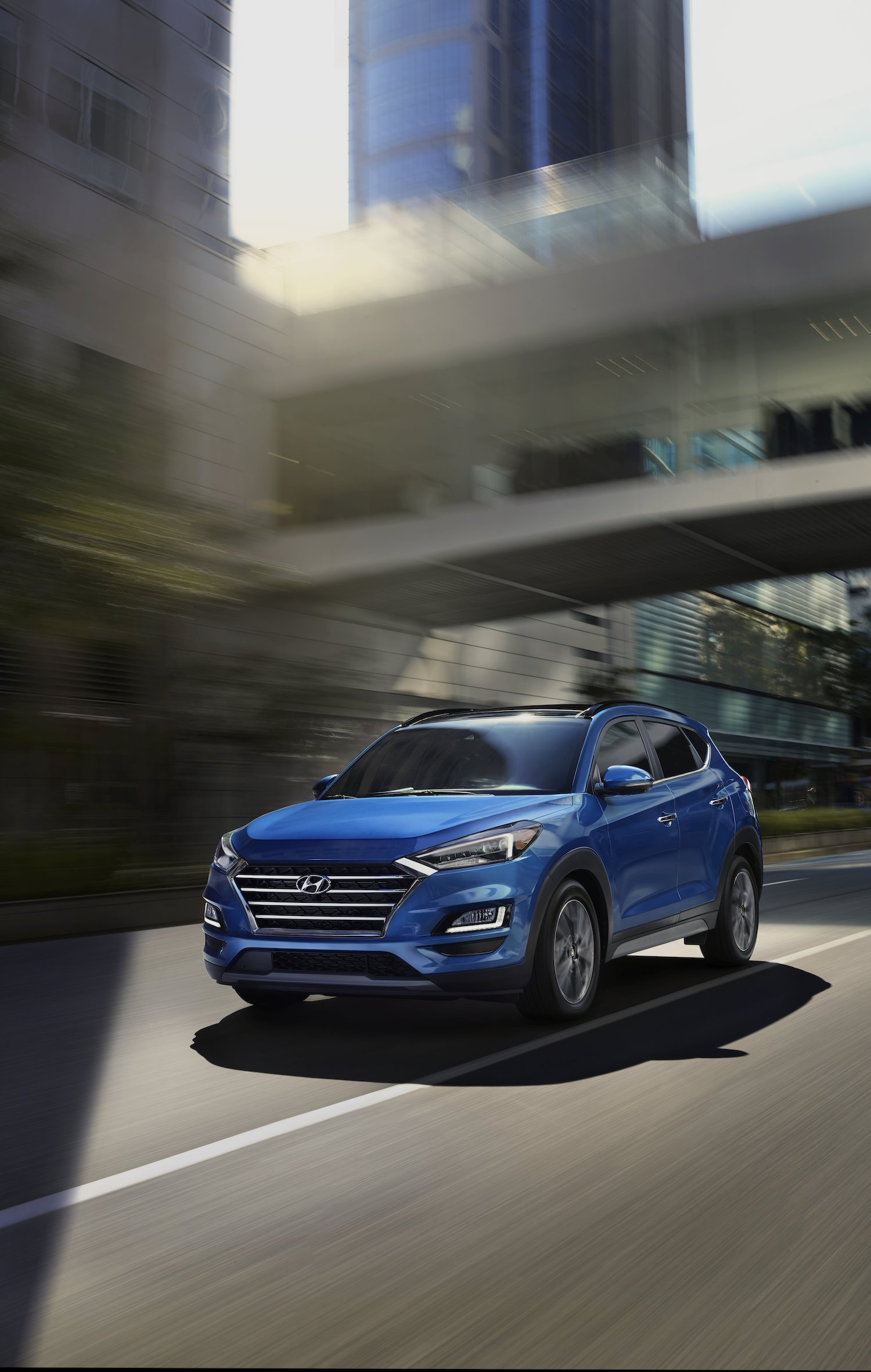 Blue hyundai tucson running on road