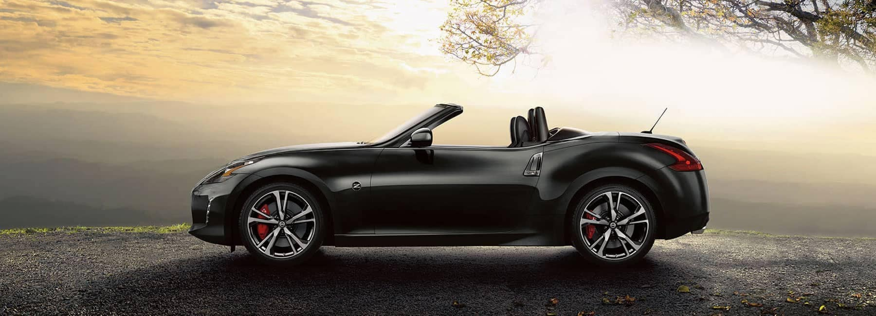 Boch Nissan is a Car Dealership near Canton, MA | Black 2019 Nissan 370Z Convertable parked at sunset