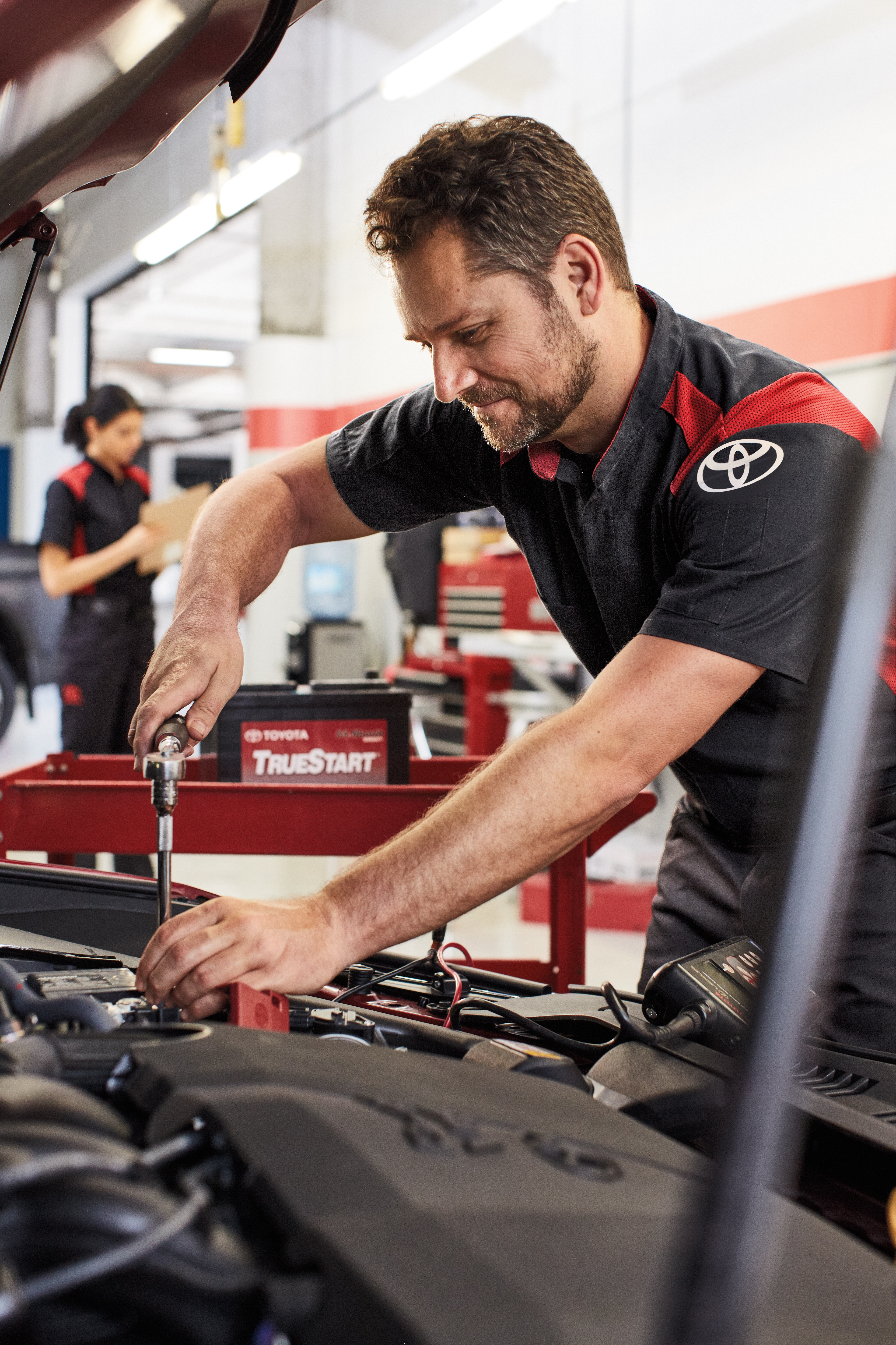 Boch Toyota is a Family Owned Dealership near Boston, MA | Toyota mechanic replacing battery in vehicle