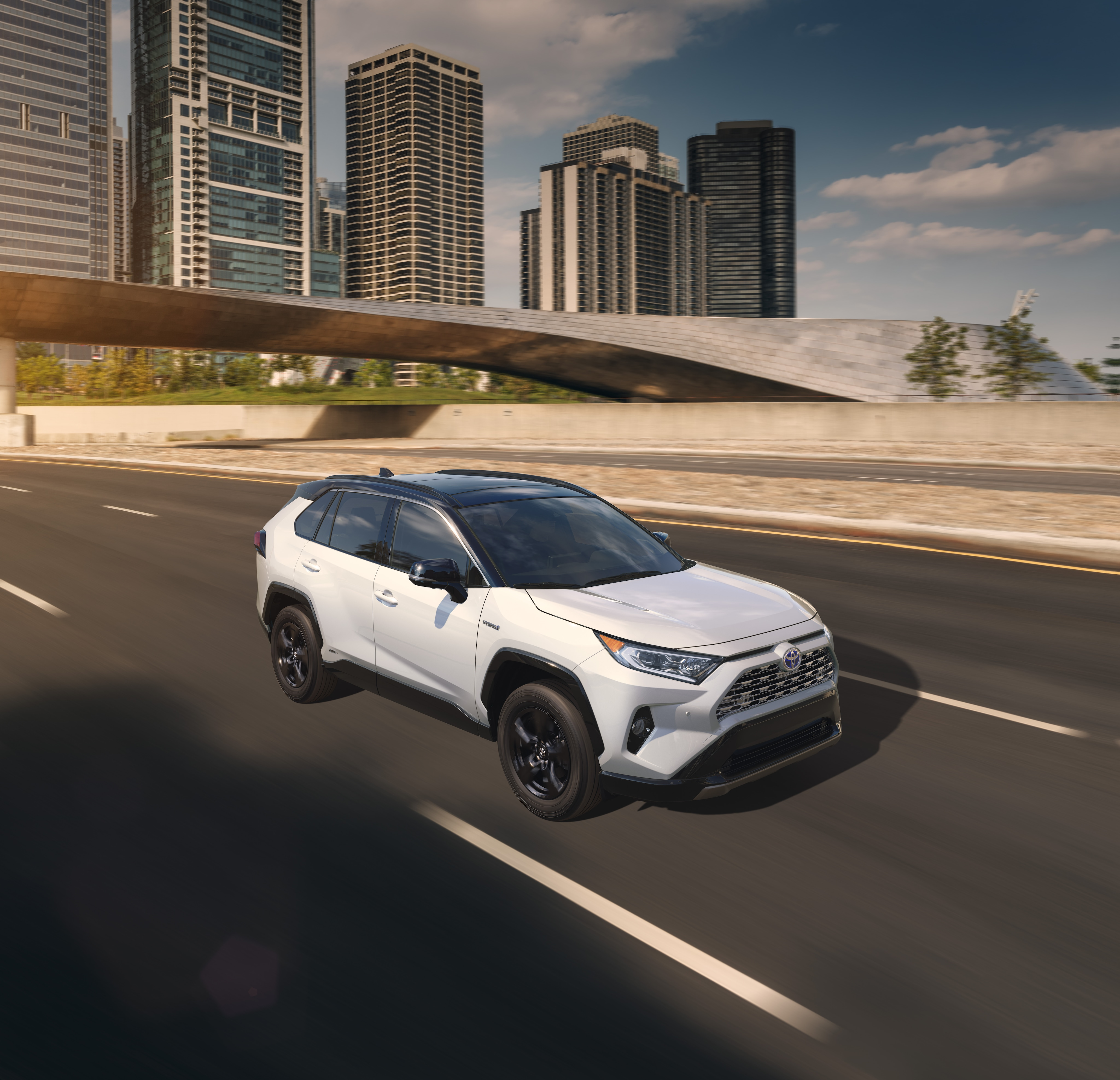 Boch Toyota is a Family Owned Dealership near Boston, MA | 2020 Toyota RAV4 driving on road with city visible in background