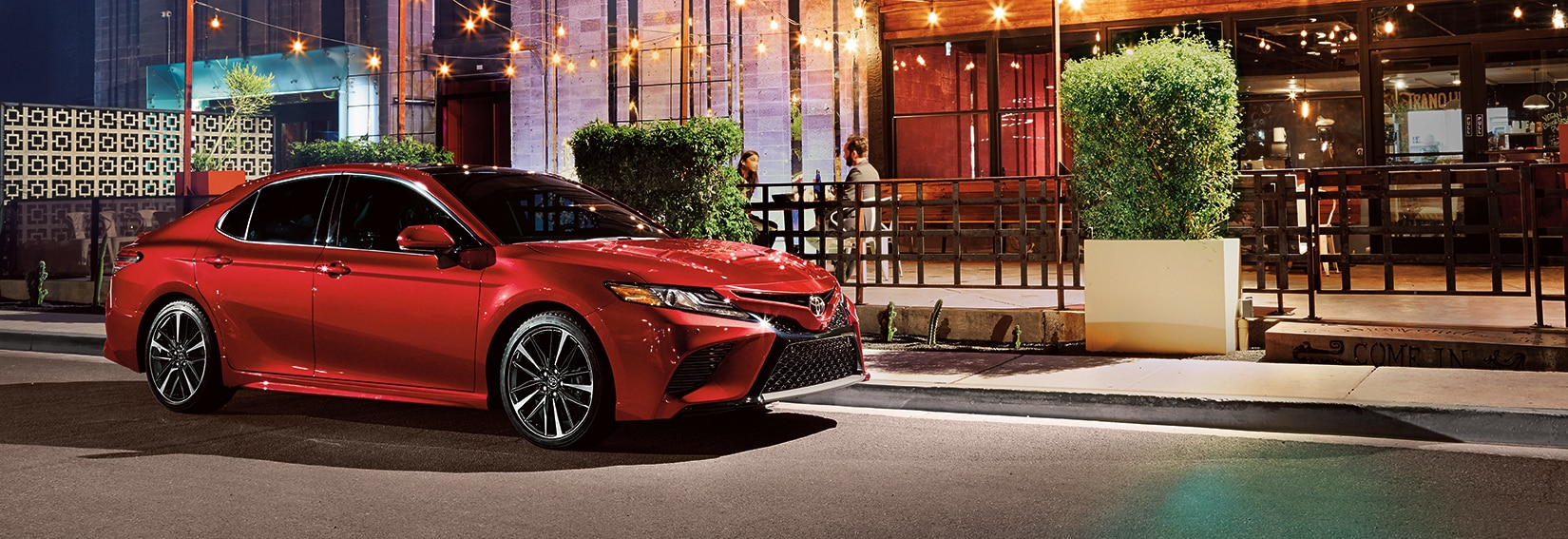 Boch Toyota is a Family Owned Dealership near Boston, MA | 2020 Toyota Camry parked outside of restaurant at night