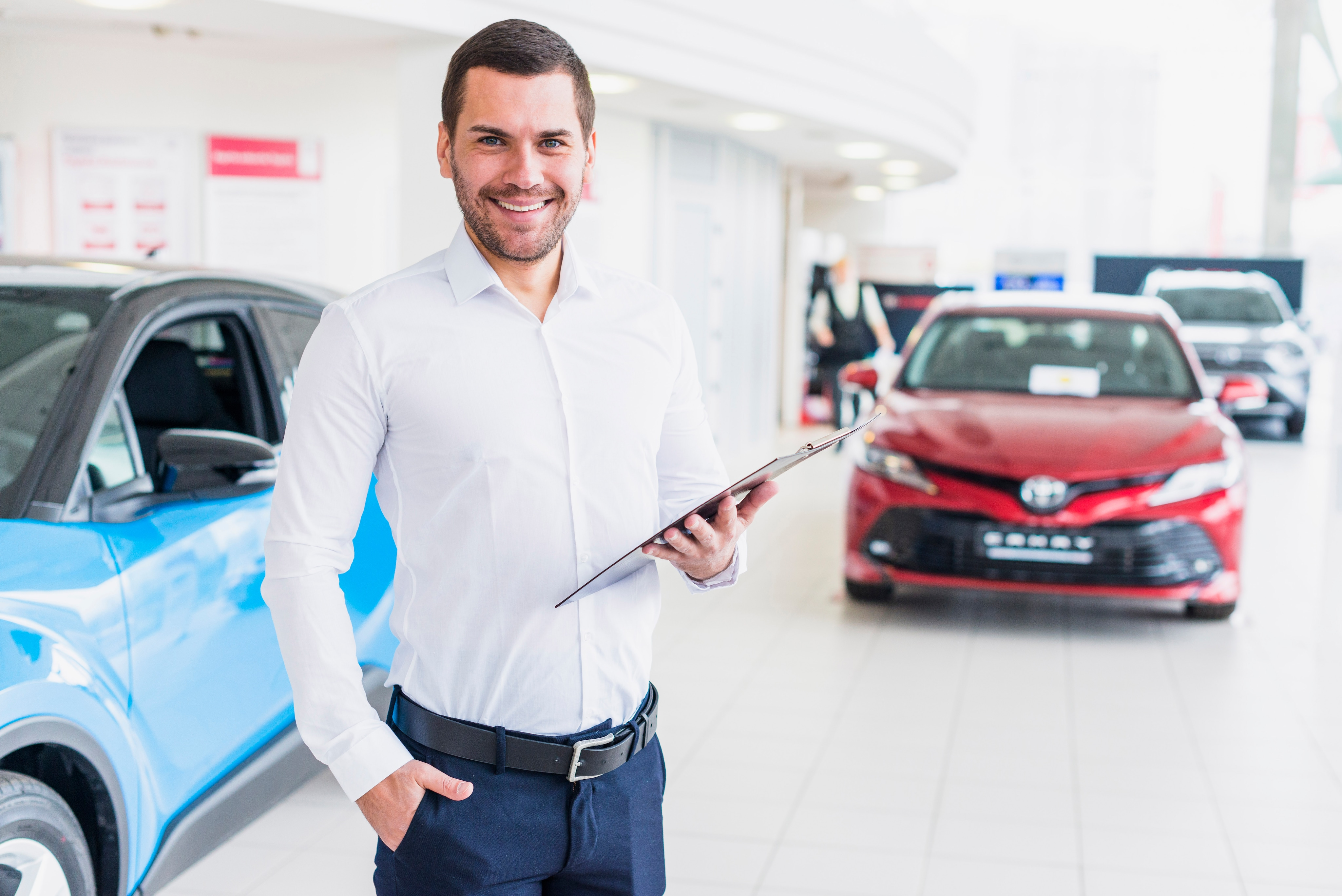 Boch Toyota is a Family Owned Dealership near Boston, MA | Toyota car salesman standing in dealer showroom holding clipboard