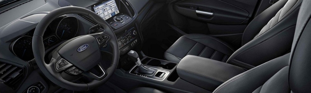 Close up view of the interior of the front of a 2019 Ford Escape SUV showcasing the sleek black interior style with a modern touch screen entertainment system