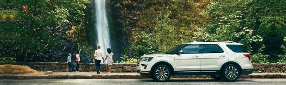 Driver side angle of a white 2019 Ford Explorer parked on the side of the road by a waterfall as the family gets out to enjoy the view