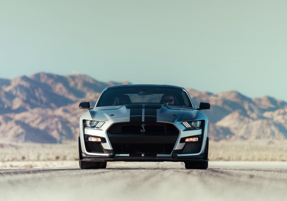 A fierce, front facing, silver 2020 Shelby Mustang GT500 parked on a desert road with pink and purple mountains behind it.