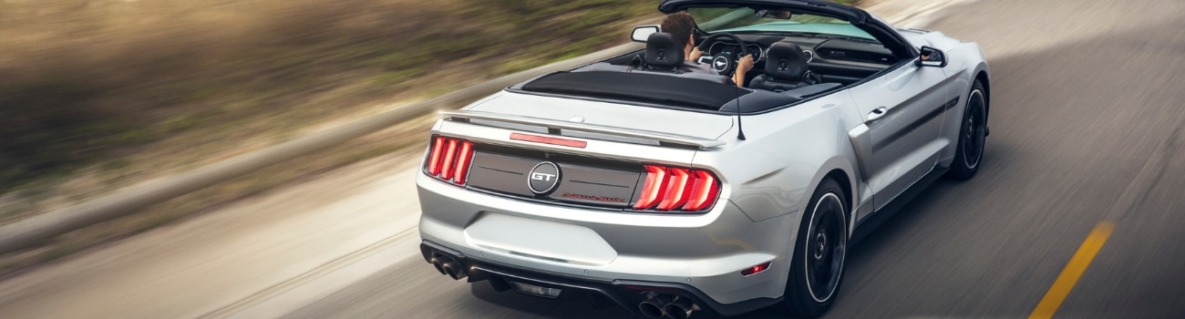 Rear angle of a silver 2019 Ford Mustang Convertible driving fast down an open highway alongside the ocean as the street lines blur around the vehicle