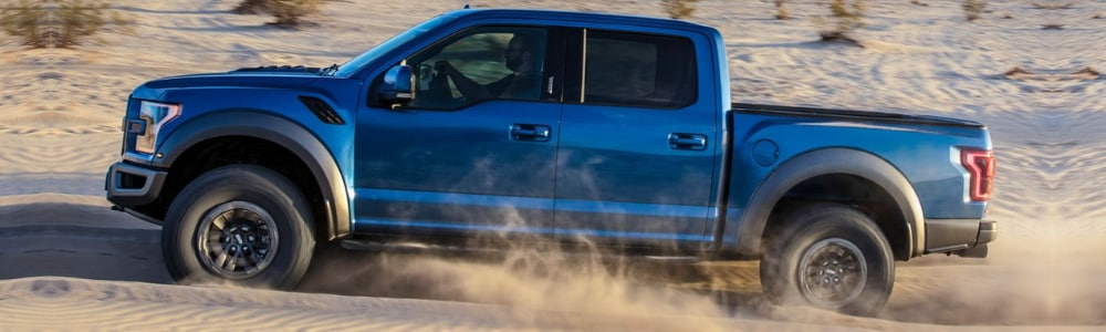 Driver side view of a blue 2019 Ford F-150 driving through sandy dunes with tires spinning kicking up dust clouds behind the wheels of the ford truck