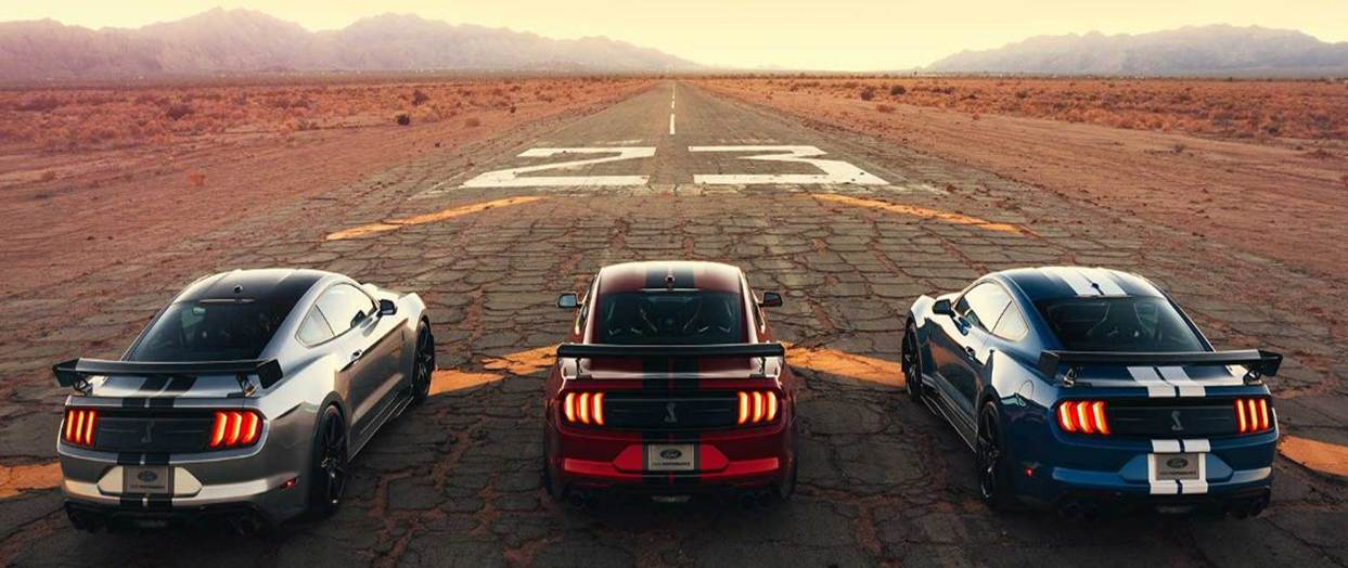 Back view of three 2020 Ford Shelby Mustang GT500s, one silver, red, and blue on a dusty, cracked desert road with a worn, white number 23 in front. Mountains in the distance frame a straight, never-ending road.