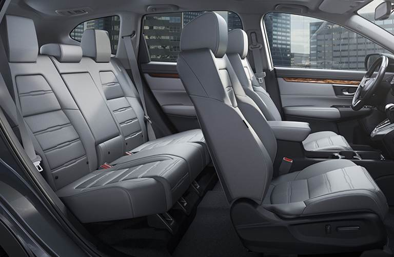 light-grey, leather interior 5 person seating of a 2019 Honda CR-V with city view