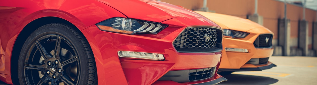Close up angle of the front passenger side of a red 2019 Ford Mustang with a slightly out of focus yellow 2019 Ford Mustang in the background