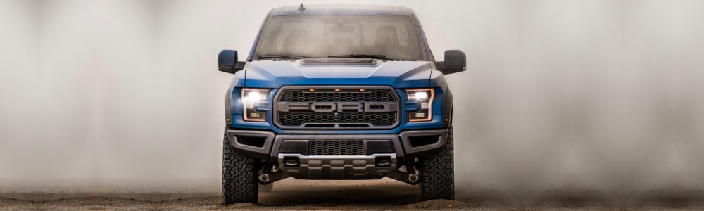 The front view of a blue 2019 Ford F-150 Raptor as it drives into the camera lens on a sandy path with heavy dust clouds surrounding the ford truck