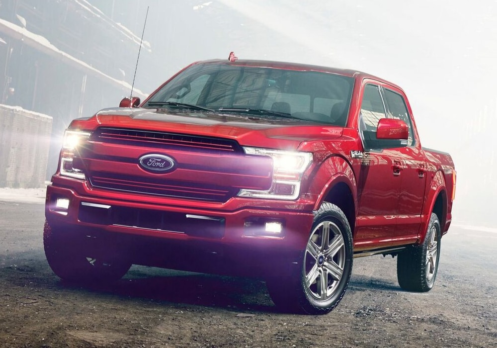 Front angle of a ruby red 2019 Ford F-150 driving through a dirt lot on a very foggy day with LED headlights shining bright