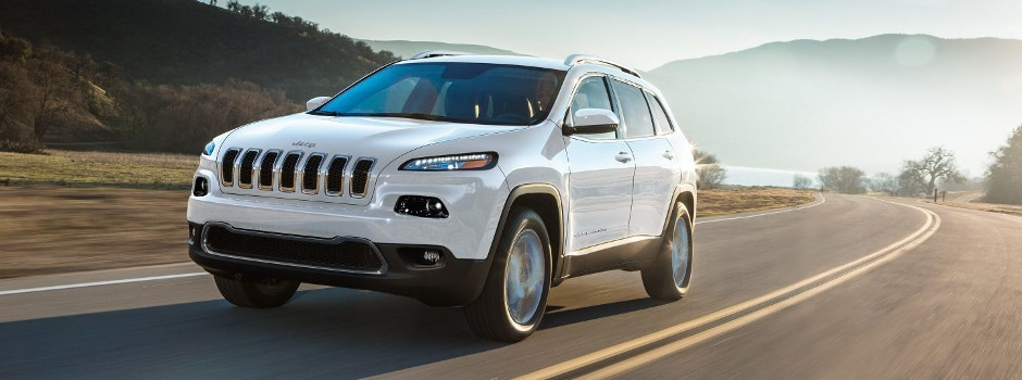 A white 2018 Jeep Cherokee driving through the countryside