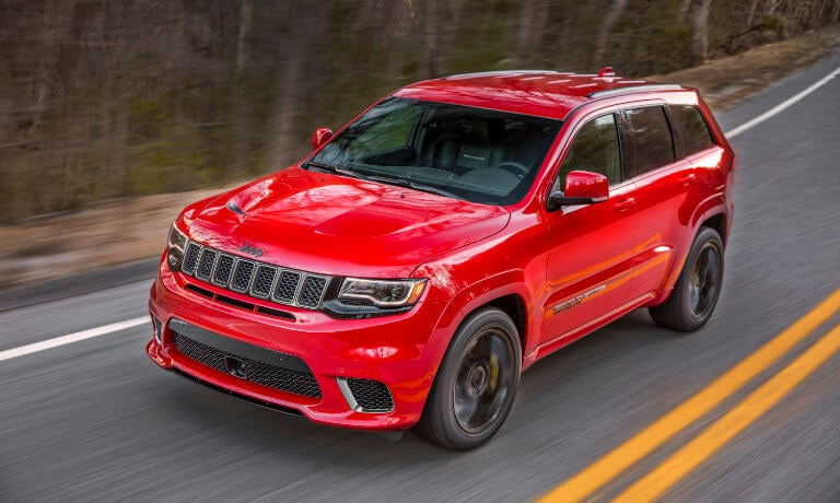 2021 Jeep Grand Cherokee exterior driving through forest highway