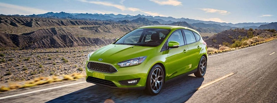 A green 2018 Ford Focus driving down the open road