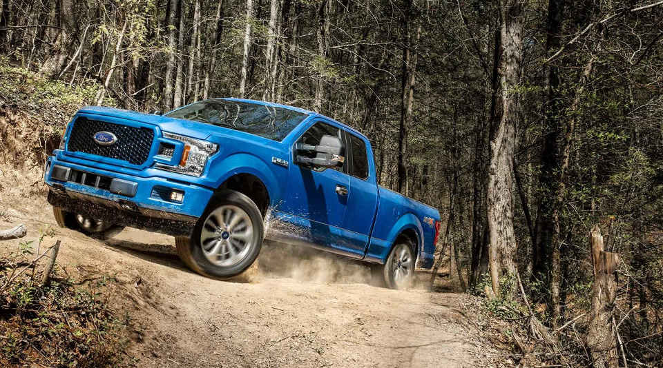 A blue 2018 Ford F-150 driving up a dusty hill
