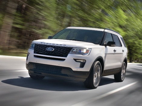 A white 2018 Ford Explorer driving down an open road
