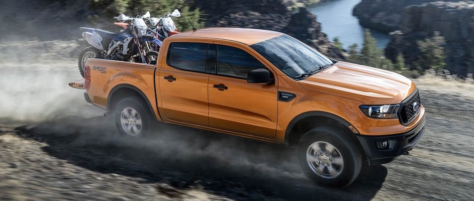 An orange 2019 Ford Ranger carrying two motorcycles