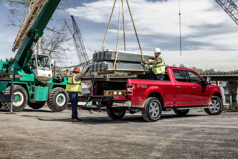 A red 2018 Ford F-150 being loaded up with metal frames