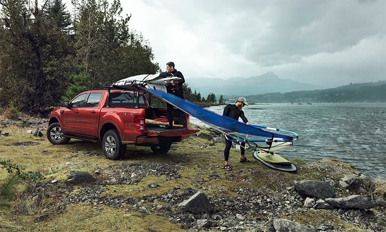 2019 Red Ford Ranger Loading a Surf Board into The Truck Bed