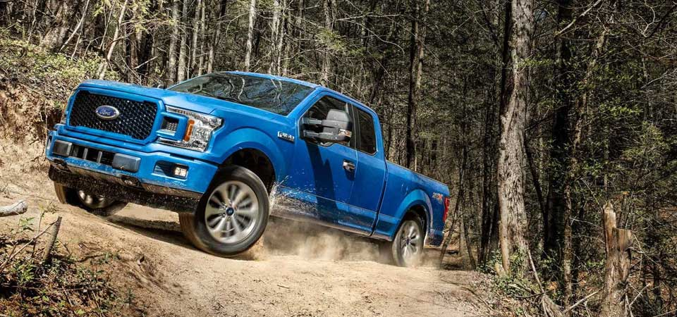 A 2018 Ford F-150 driving in the woods