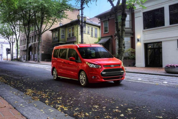 A red 2018 Ford Transit Connect driving down a city street