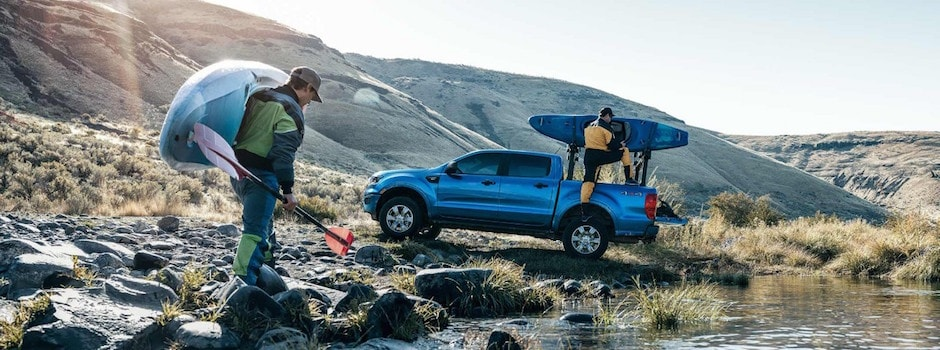 Two men bringing their kayaks to their blue 2019 Ford Ranger