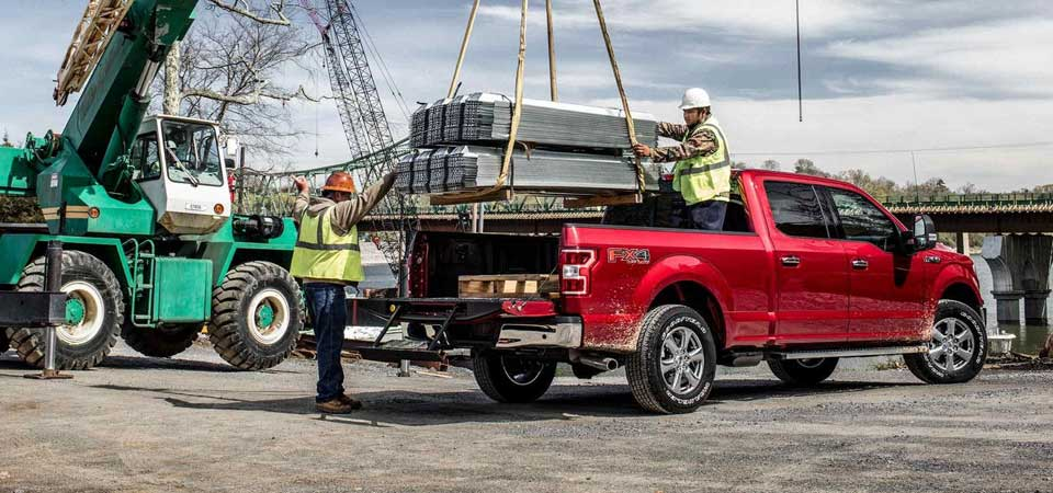 Workers loading wood into the back of a 2018 Ford F-150