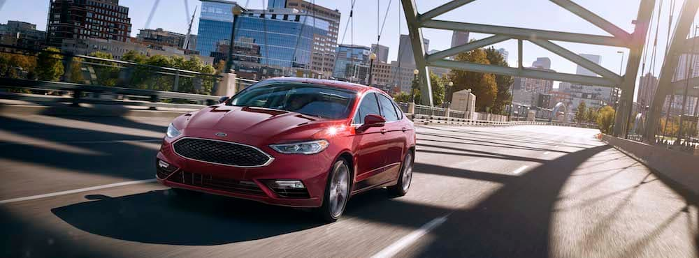 Red Ford Fusion Driving Over A Bridge