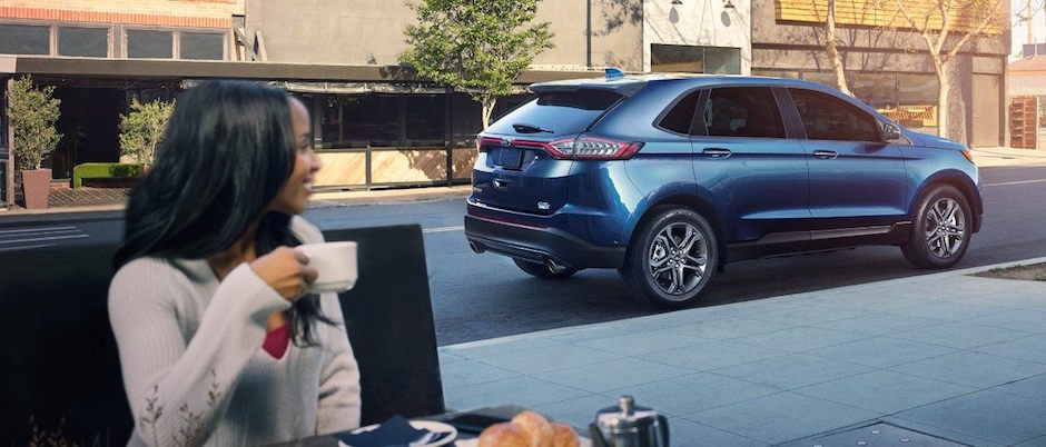 A woman having coffee in front of her Ford Edge