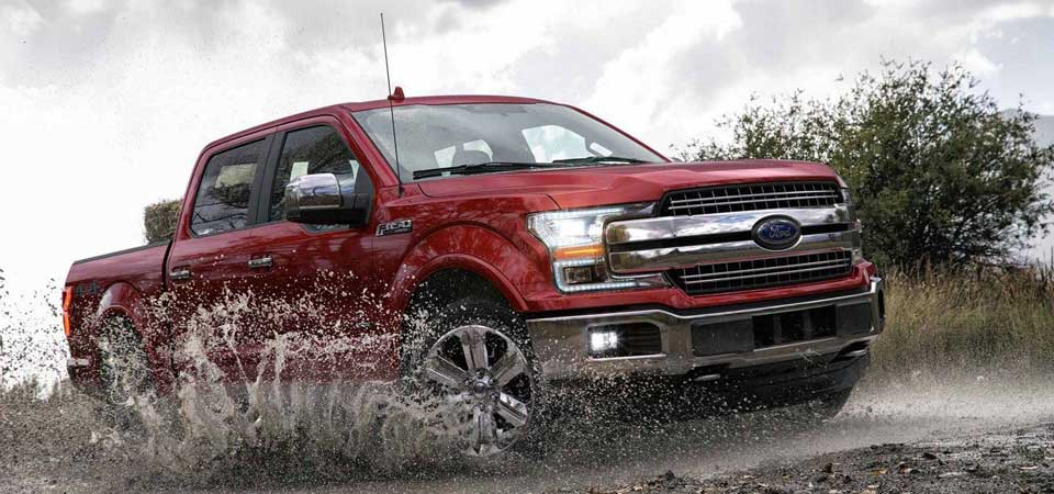 A red Ford F-150 driving through mud