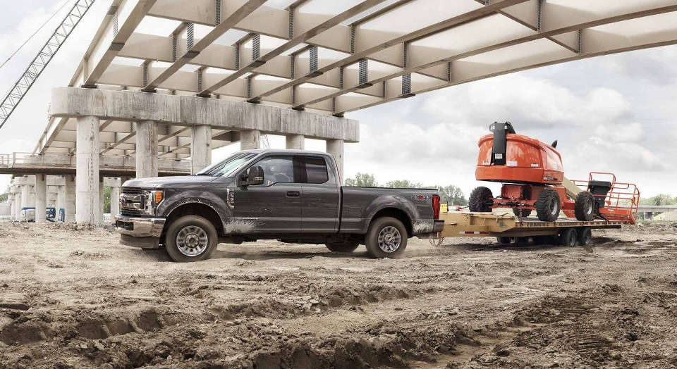 A grey 2018 Ford F-250 towing large machinery