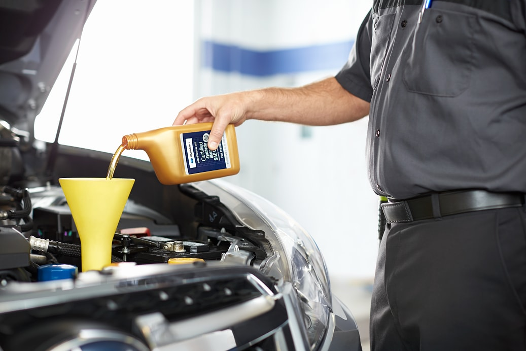 Subaru service tech pouring oil