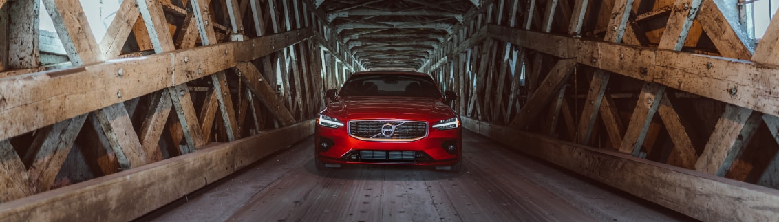 Red Volvo S60 on wooden bridge