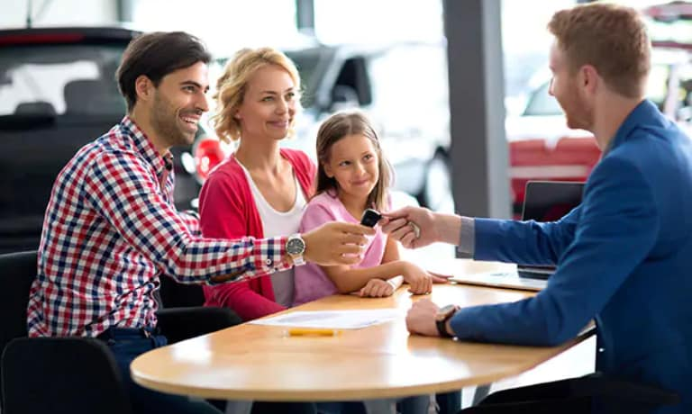 Sales Consultant handing a family the keys