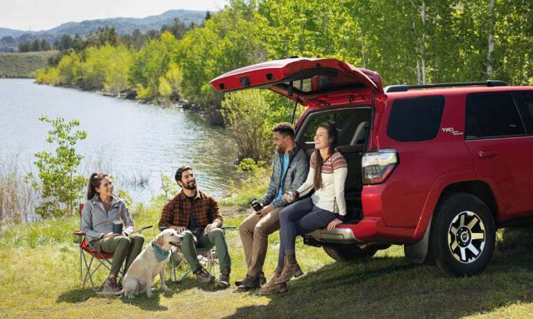Red 2020 Toyota 4Runner parked by a lake with two couples camping